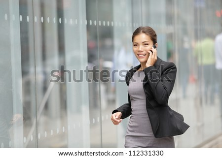 Businesswoman on cellphone running while talking on smart phone. Happy smiling mixed race Asian / Caucasian business woman busy. Image from Manhattan, New York City. - stock photo