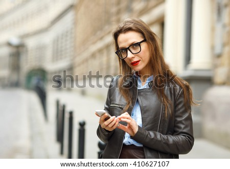 Businesswoman on cellphone walking down the street while talking on smart phone. Modern caucasian business woman busy
