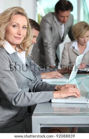 Businesswoman on laptop smiling - stock photo