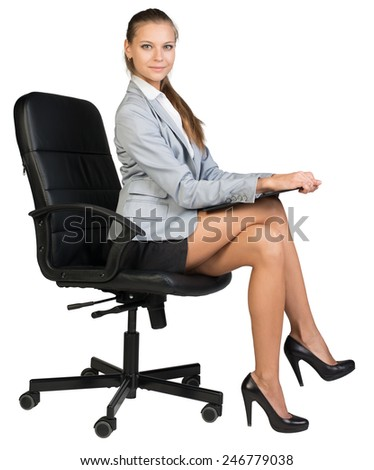 Businesswoman on office chair, holding clipboard or folder on her knees, looking at camera cheerfully. Isolated over white background - stock photo