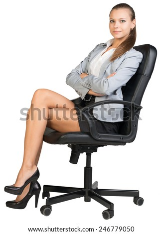 Businesswoman on office chair, looking at camera, with her back straight and her arms crossed on her breast. Isolated over white background - stock photo