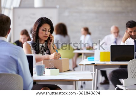 Businesswoman On Phone Arranging Collection Of Package - stock photo