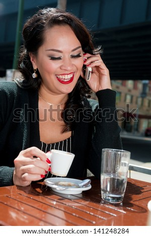 Businesswoman on phone during coffee break in NYC - stock photo