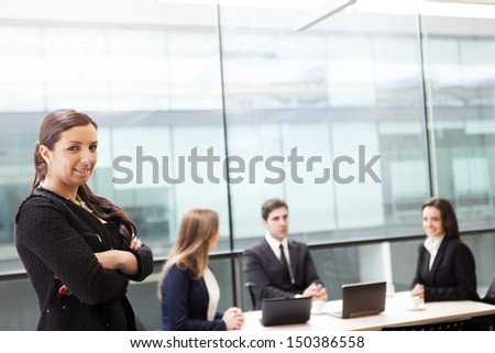 Businesswoman on the foreground of her team - stock photo