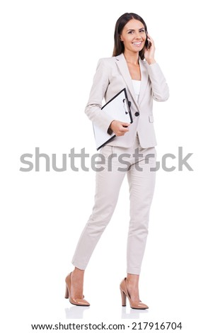 Businesswoman on the Go. Full length of confident young businesswoman in suit talking on the mobile phone and holding clipboard while walking against white background  - stock photo