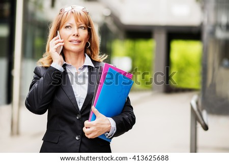 Businesswoman on the phone outdoors.Mature businesswoman with a folder at the office building. - stock photo