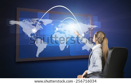 Businesswoman operating touch screen interface featuring world map with flight paths or trade routes or communication between countries and cities and on blue background - stock photo
