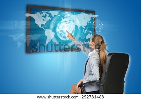 Businesswoman operating touch screen interface with world map, on blue background - stock photo