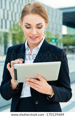 businesswoman or female manager using pad or tablet computer and is reading or presenting on it - stock photo