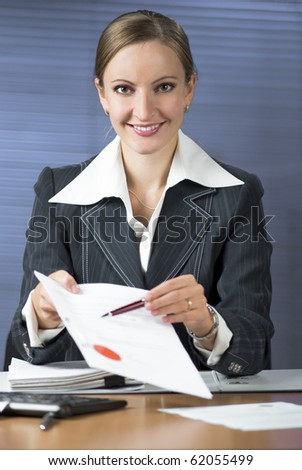 Businesswoman (or notary public) holding pen pointing at signature place on a contract document - stock photo