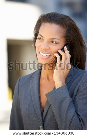 Businesswoman Outside Office On Mobile Phone - stock photo
