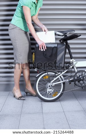 Businesswoman packing bag on the back of folding commuter bicycle, side view, low section