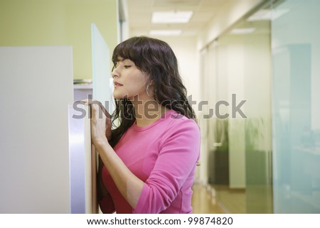 Businesswoman peeking over the partition