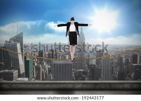 Businesswoman performing a balancing act against balcony overlooking city