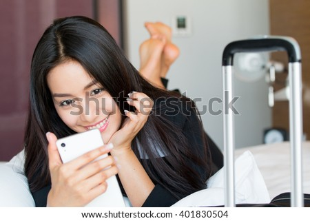 Businesswoman playing mobile phone on the bed in the hotel. - stock photo