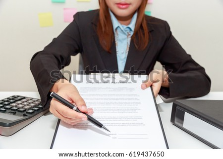 Businesswoman pointing a place where should sign the employment agreement.