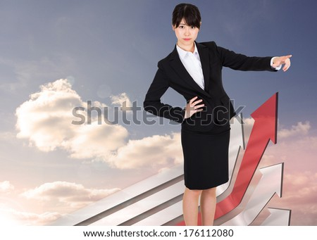 Businesswoman pointing against red and grey curved arrows pointing against sky