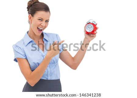 Businesswoman pointing at alarm clock with finger
