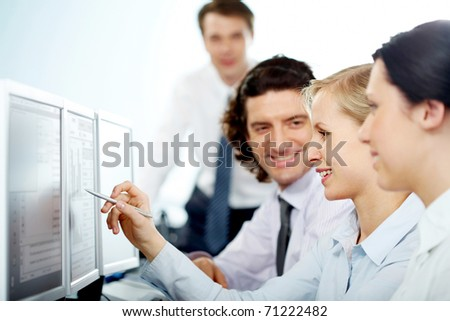 Businesswoman pointing at computer monitor showing it to her colleagues - stock photo