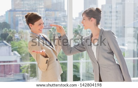 Businesswoman pointing at her rival by large window - stock photo