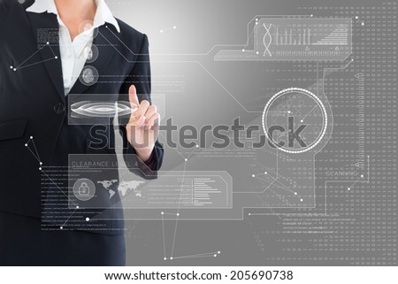 Businesswoman pointing at interface against grey vignette - stock photo