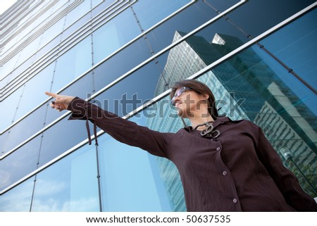 businesswoman pointing away next to her office building