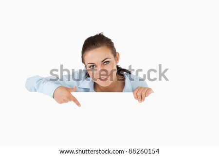 Businesswoman pointing on sign under her against a white background - stock photo