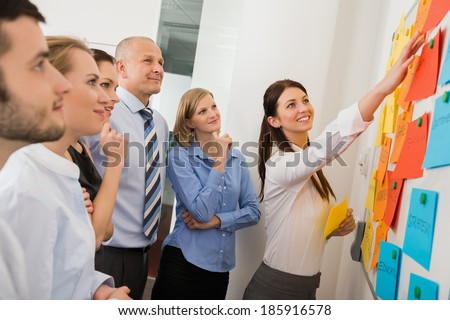 Businesswoman pointing  on whiteboard in meeting with office colleagues