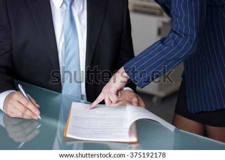 Businesswoman pointing to contract, boss sign document in office