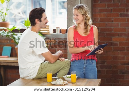 Businesswoman pointing towards digital table while looking at colleague in creative officee - stock photo