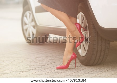 Businesswoman posing near white car and showing her slim and slender legs near her car. Successful lady in grey skirt posing on pink high heels. Toned image. - stock photo