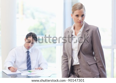 Businesswoman posing while her colleague is working in a meeting room - stock photo