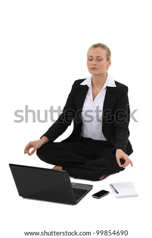 Businesswoman practicing yoga in front of her laptop - stock photo