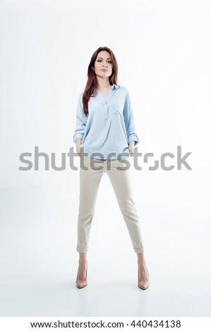businesswoman. prepares to join the adult life. full of confidence and optimism. studio shot. White background. breeches, blue shirt. expensive watches. healthy skin. - stock photo