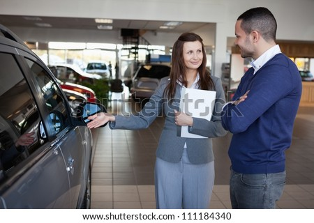 Businesswoman presenting a car to a client in a dealership