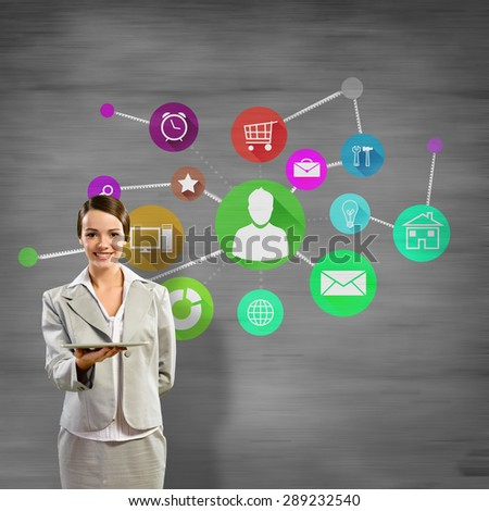Businesswoman presenting tablet pc and color icons at background - stock photo