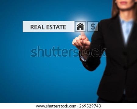 Businesswoman pressing real estate button on virtual screens.Women finger on home icon. Isolated on blue. Business, technology, internet and networking concept - Stock Image