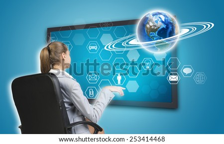 Businesswoman pressing touch screen button on virtual interface with Globe and hexagons with icons, on blue background. Element of this image furnished by NASA