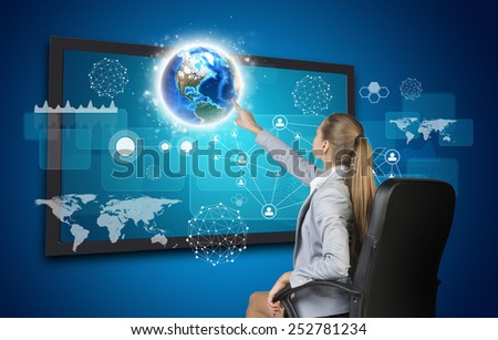 Businesswoman pressing touch screen button on virtual interface with Globe and other elements, on blue background. Element of this image furnished by NASA