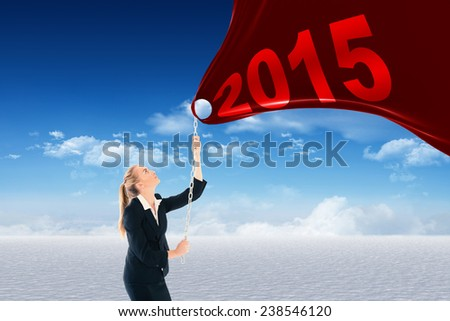 Businesswoman pulling a chain against snowy landscape under blue sky