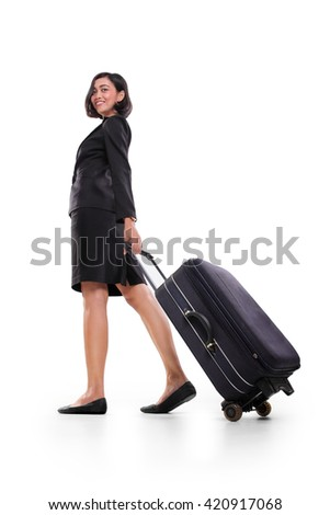 Businesswoman pulling a suitcase and walking away, full body shot isolated on white background