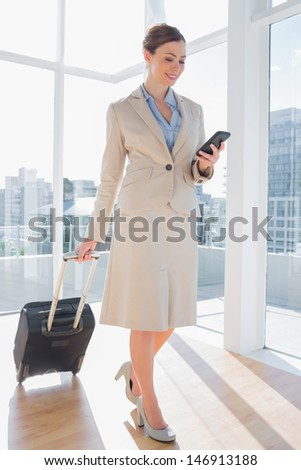 Businesswoman pulling her suitcase and checking her phone in bright office - stock photo