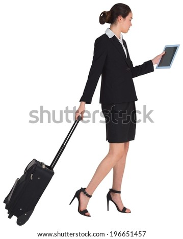 Businesswoman pulling her suitcase holding tablet on white background
