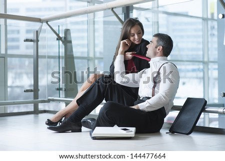Businesswoman pulls male coworker towards her with his tie - stock photo