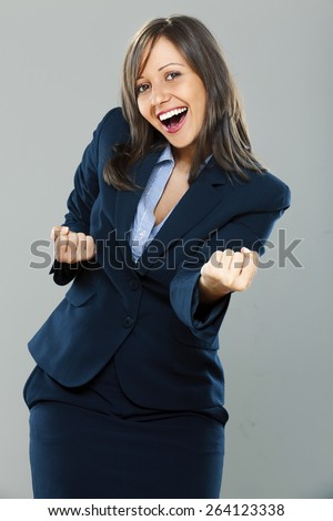 Businesswoman punching the air full of joy isolated on gray background, expressing success - stock photo