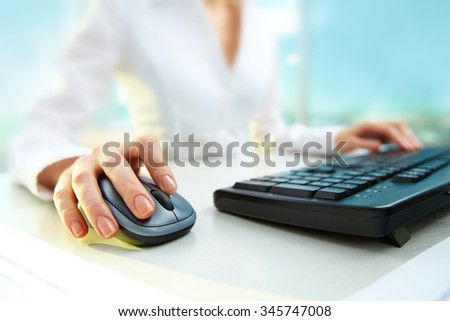 Businesswoman pushing key of a computer mouse while typing - stock photo