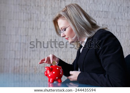 Businesswoman put coins into red dotted piggy bank, saving - stock photo