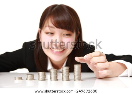 Businesswoman put coins to stack of coins - stock photo