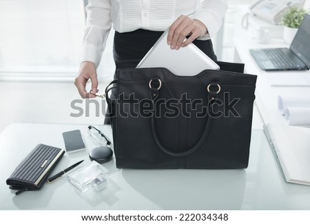 Businesswoman putting essential things into her handbag, starting with tablet computer  - stock photo