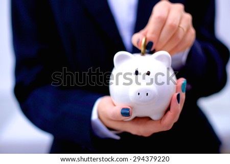 Businesswoman putting  money into a piggy bank isolated on white background